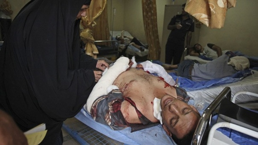 Aug. 17: An injured man is comforted by his mother at a hospital in Baghdad following a deadly homicide blast.