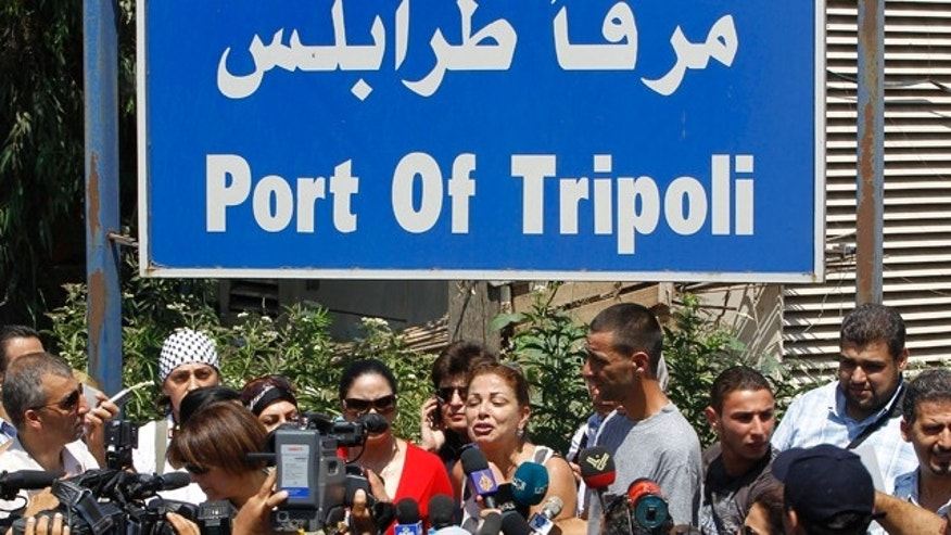 Aug. 19: Lebanese Samar al-Hajj, center, one of the organizers of Mariam ship that plans to sail to Gaza Strip, speaks during a press conference outside the seaport of Tripoli in Lebanon. (AP photo)