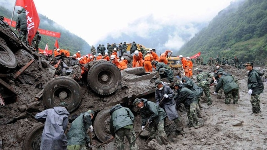 In this photo released by China's Xinhua news agency, rescuers clear off sludge in mudslide-hit Puladi township, southwest China's Yunnan province, on Friday Aug. 20, 2010. China struggled to cope with widespread storms that left dozens missing and presumed dead Thursday as rescuers cleaned up a mudslide-stricken town, while two passenger train cars plunged into a river after crossing a flood-damaged bridge.