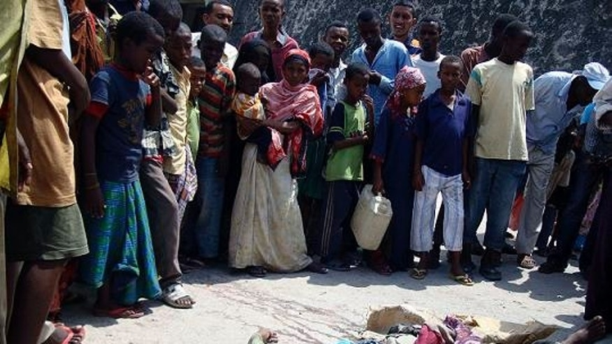 Residents in Mogadishu, Somalia, look at the dead body of a man, Somali government claimed to be an Islamist militant who was killed by a bomb. (AP)