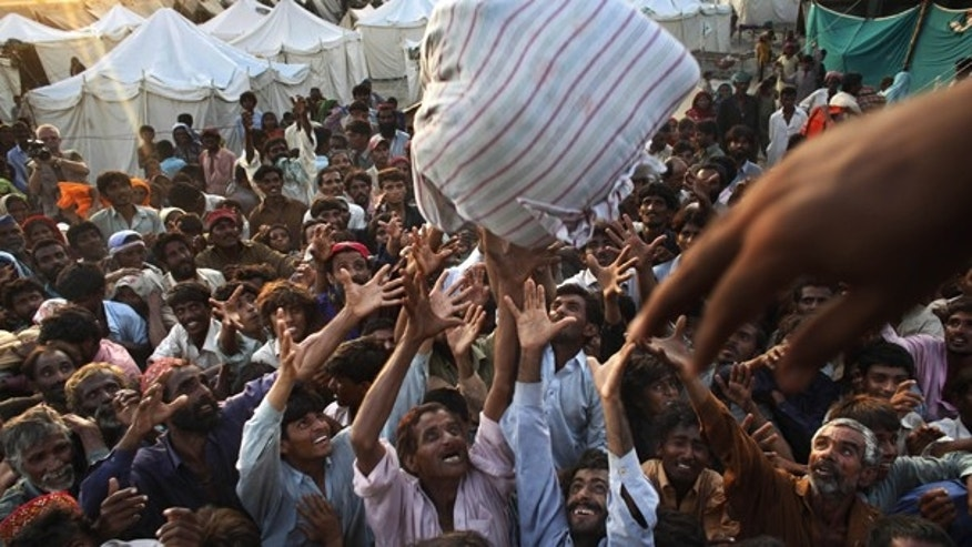 Aug. 19: People displaced by flooding fight for blankets during an aid distribution by the Pakistani Air Force at a temporary camp set up for residents who had to flee their homes in southern Pakistan.