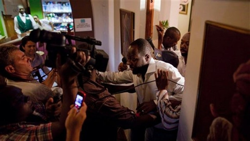 Aug. 20: Haitian-born singer and presidential candidate Wyclef Jean, right, exits a hotel room after Haiti's Electoral Council rejected his presidential candidacy in Port-au-Prince, Haiti, on Friday.