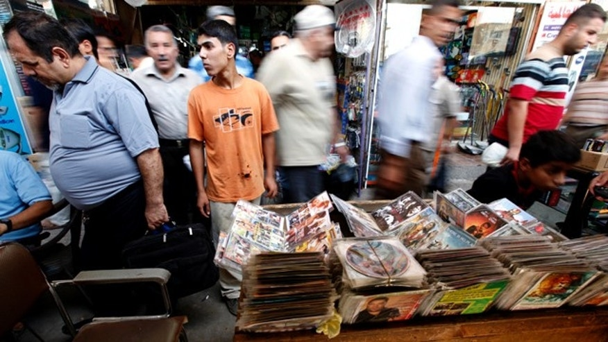 July 22: Iraqis walk past a street vendor selling DVD movies in central Baghdad, Iraq. The nude women on the DVD covers in a Baghdad street stall say it all: Change, whether you like it or not, is afoot in Iraq. (AP)