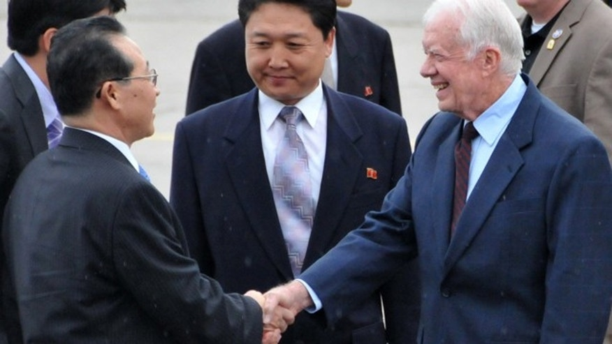 Aug. 25: Former U.S. President Jimmy Carter, front right, shakes hands with North Korea's Vice Minister of Foreign Affairs Kim Kye Gwan, at the airport in Pyongyang.