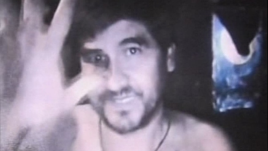 Aug. 26: This image made from video shows one of the trapped Chilean miners in the underground chamber.