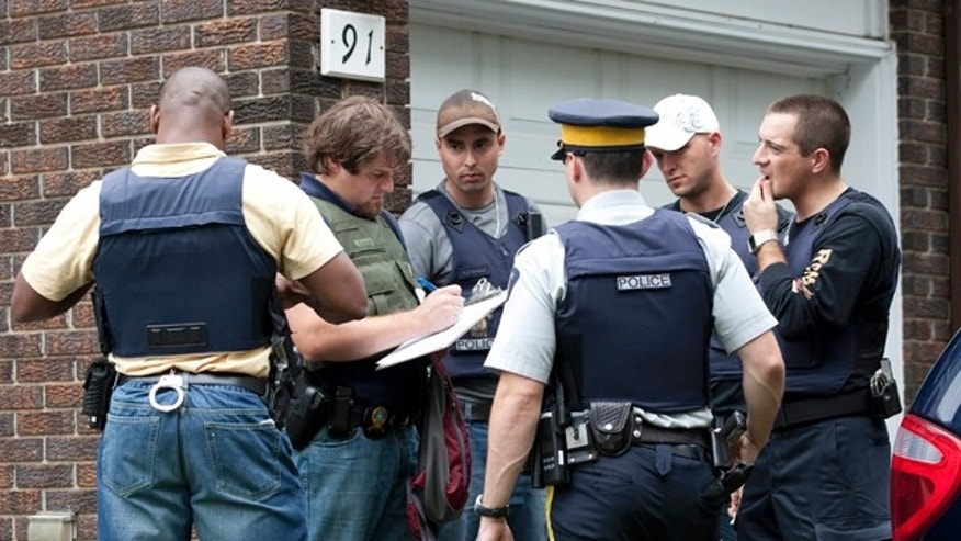 Aug. 25: Police talk outside of a home in the west end of Ottawa, Canada, after police arrested two Ottawa residents on terror-related charges.