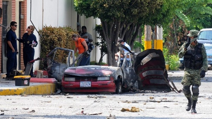 Aug. 27: Investigators work at the site of an exploded car outside the Televisa network in Ciudad Victoria, Mexico.