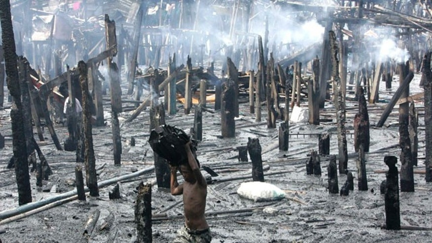 August 27: A resident of the coastal township of Navotas, north of Manila, sifts through the debris following a fire that gutted hundreds of homes, mostly on stilts, late Thursday in the Philippines. No casualties were reported but the fire left more than 4,000 people homeless. (AP)