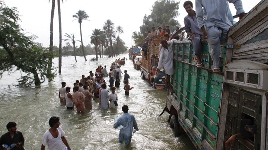 August 18: Flood survivors carry relief goods along a flooded area in Muzaffargarh, Punjab province, in Pakistan. (AP)