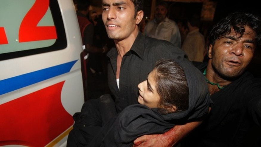 Sept. 1: Volunteers carry an injured girl to an ambulance after blasts in Lahore, Pakistan.