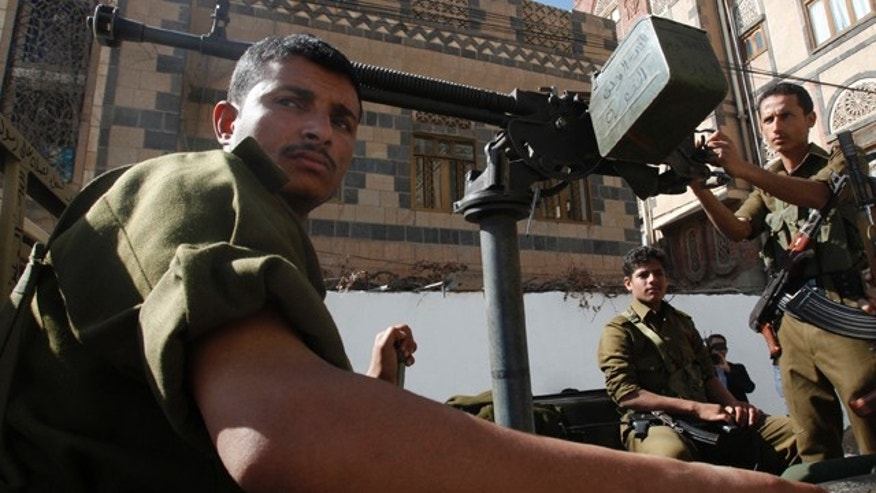 FILE: Yemeni police troopers sit on a police vehicle outside the state security court in Sanaa on Jan. 26, 2010.