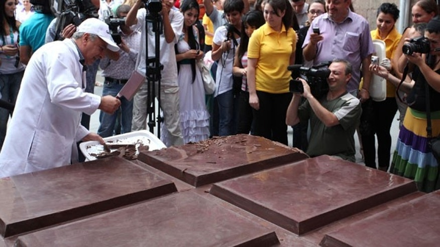 A candy factory worker chops small pieces of chocolate for people to taste, off a huge chocolate bar produced by the Grand Candy factory in the Armenian capital, Yerevan, Saturday, Sept. 11, 2010. The chocolate bar that Guinness World Records has certified as the world's biggest.