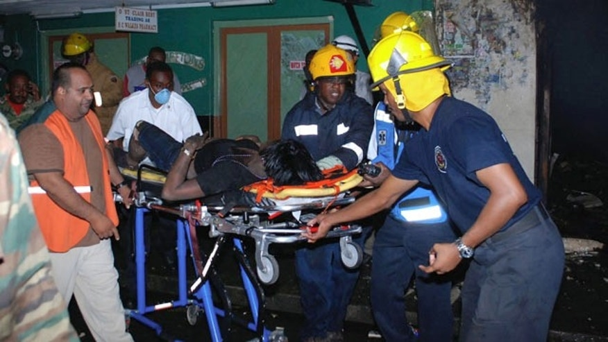September 3: Firefighters pull an injured woman from the fire at a clothing store in downtown Bridgetown, Barbados.  Two men burst into the Campus Trendz Boutique and demanded money before setting the building on fire Friday evening, killing at least six people. (AP)