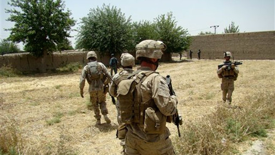 June 8: U.S. marines provide security during a government function to lay the foundations for a government administrative department building at Musa Qala in Helmand, Afghanistan.