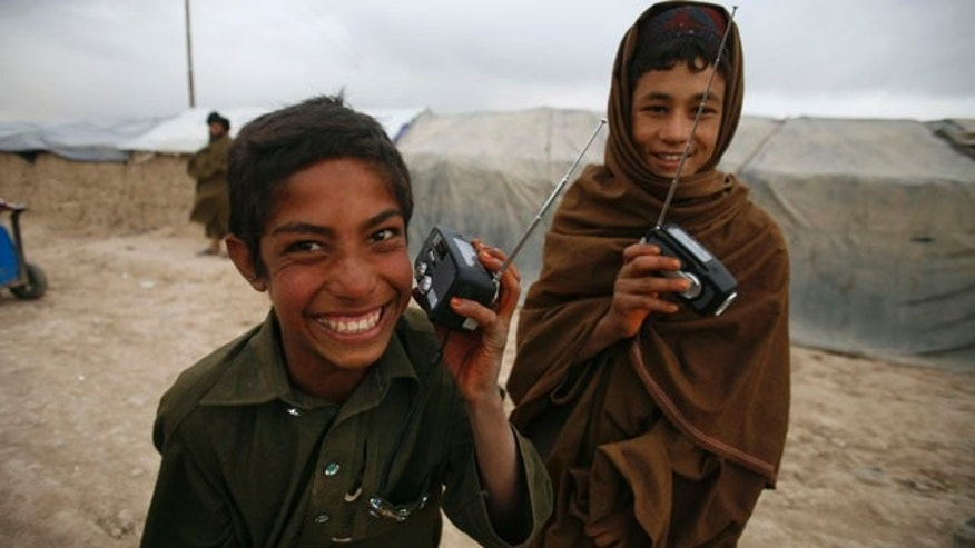 Sept. 17, 2010: nternally displaced Afghan children listen to radios distributed by Radio Free Europe/ Radio Liberty in Kabul, Afghanistan.