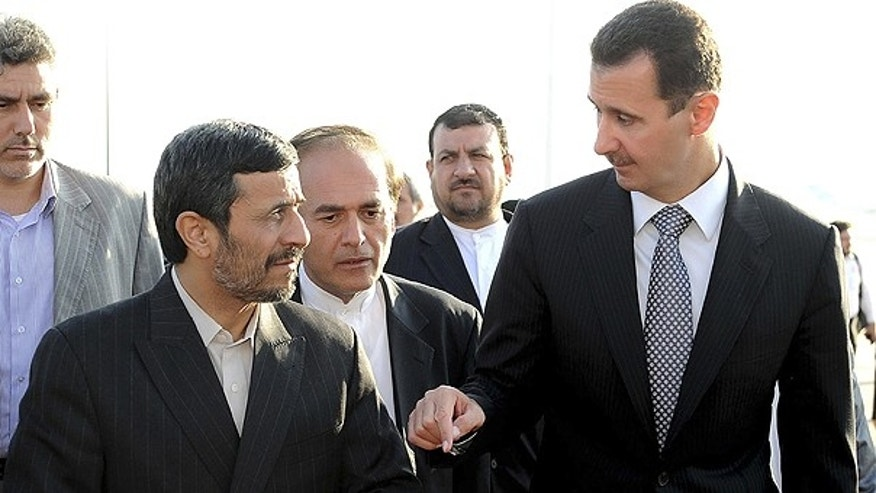 Sept. 8: A handout picture released by the official Syrian Arab News Agency (SANA) shows Syria's President Bashar al-Assad , right, welcoming his Iranian counterpart Mahmoud Ahmadinejad at Damascus airport.