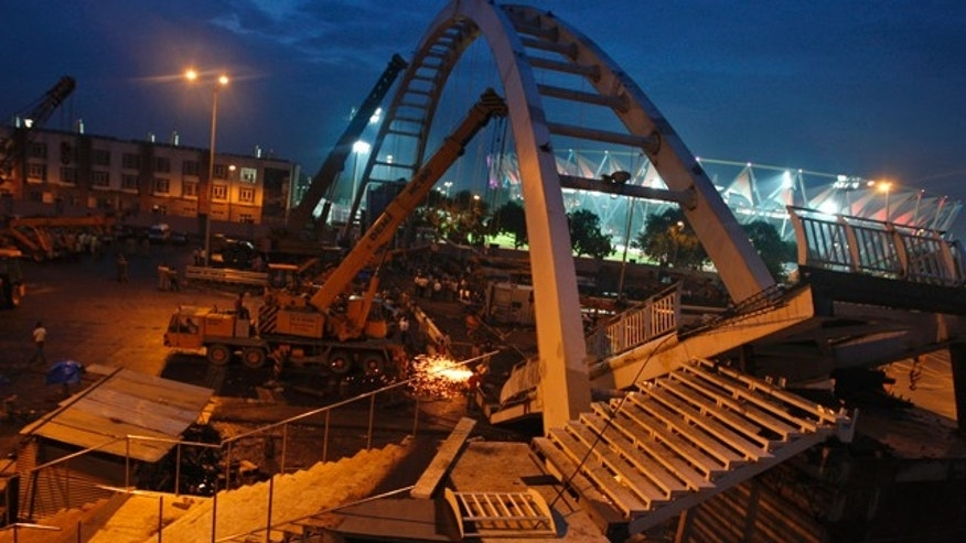 September 21: Indian workers remove debris from a collapsed bridge near an illuminated Jawaharlal Nehru stadium in New Delhi, India.  A footbridge under construction near the Commonwealth Games main stadium collapsed on Tuesday, injuring people, police said. The games are scheduled to be held from Oct. 3-14. (AP)