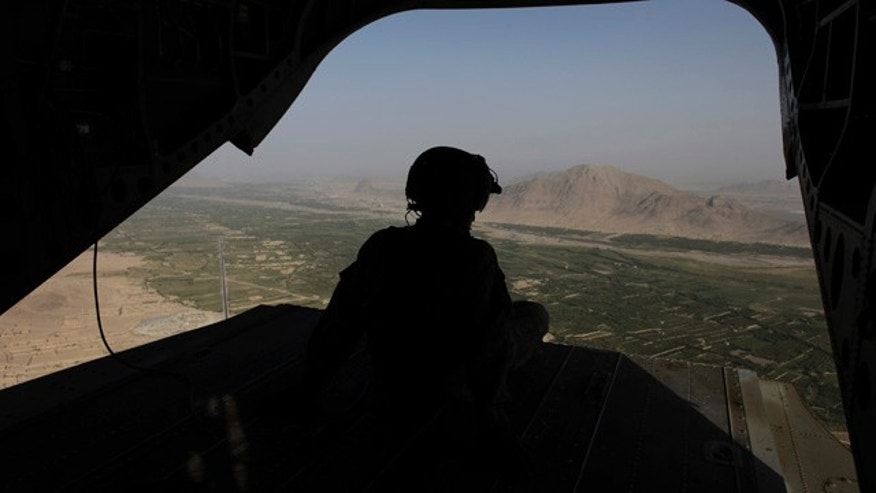 Sept. 11: A crew chief looks out the open back of a U.S. Army Chinook helicopter over Zhari district, southern Afghanistan. Nine service members with the international coalition in Afghanistan died Tuesday after their helicopter crashed in southern Zabul province.
