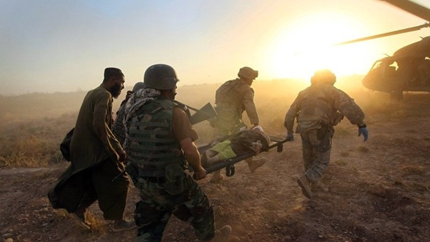Sept. 20: Coalition forces carry a wounded Afghani to a medical helicopter near Marja.