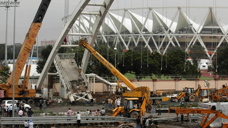 Sept. 22: A crane lifts debris from a pedestrian bridge that collapsed outside the Jawaharlal Nehru Stadium, the main venue for the Commonwealth Games, in New Delhi, India.