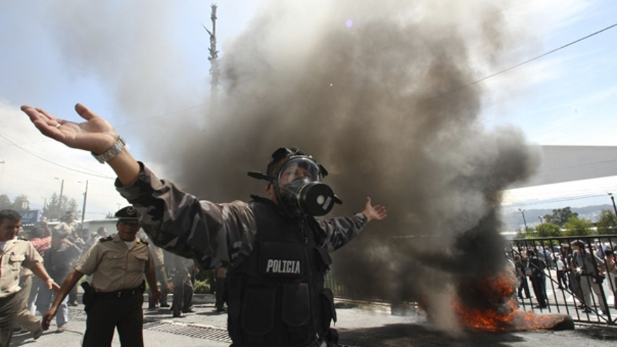 Sept. 30: A police officer demonstrates next to a bonfire during a protest of police officers and soldiers against a new law that cuts their benefits at a police base in Quito, Ecuador.