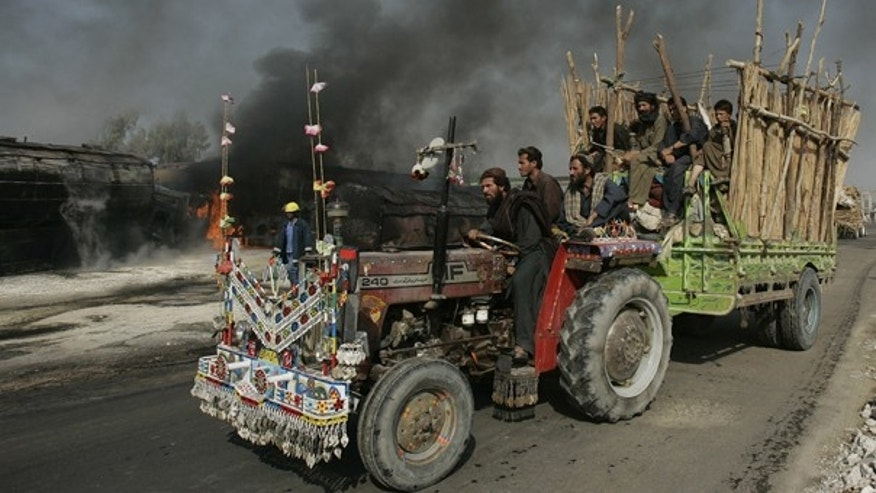 Oct. 1: Flood affected residents pass by the still smoldering oil trucks in Shikarpur, southern Pakistan. The country is urging the West that trade, not aid, will help it recover from the floods and stop its militant activity.