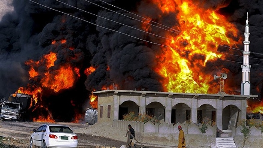 Oct. 6: Pakistani fire fighters gather next to burning oil tankers after militants attacked a terminal in Quetta.