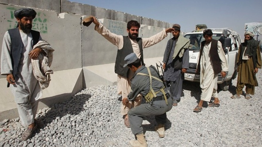 Oct. 6, 2010: An Afghan policeman checks passengers of a vehicle at a joint U.S. and Afghan military checkpoint in the outskirts of Kandahar. Afghan police say they have intercepted 22 tons of explosives reportedly imported from neighboring Iran.