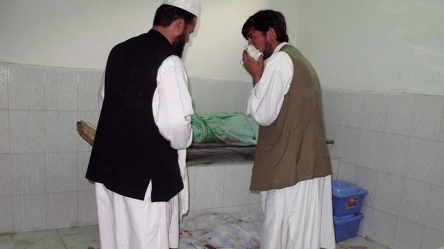 Oct. 8: Afghans stand by bodies of people killed in a bombing in a mosque in Taloqan, north of Kabul, Afghanistan.