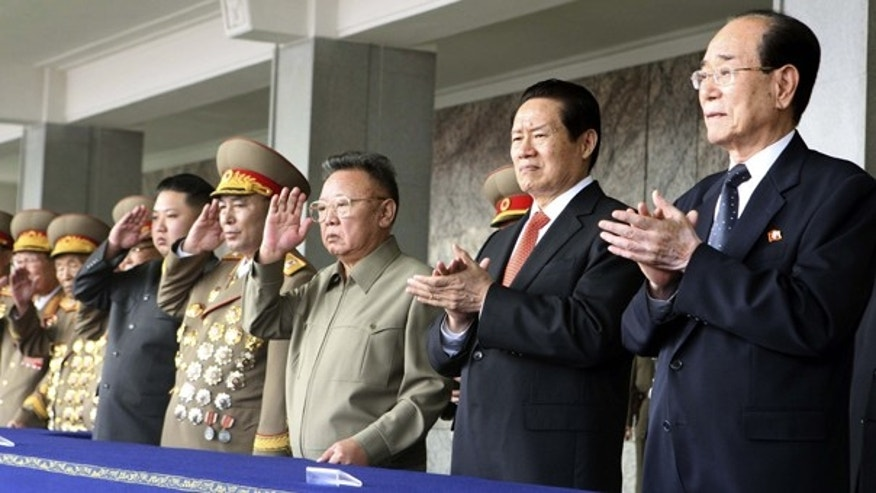 Oct. 10: In this photo released by China's Xinhua News Agency, Kim Jong Un, fourth from left, salutes while standing with his father North Korean leader Kim Jong Il, center and Zhou Yongkang, second from right, a member of the Standing Committee of the Political Bureau of the Communist Party of China (CPC) Central Committee, as they watch a massive military parade to celebrate the 65th anniversary of the founding of the Workers' Party of Korea (WPK), in Pyongyang, North Korea.