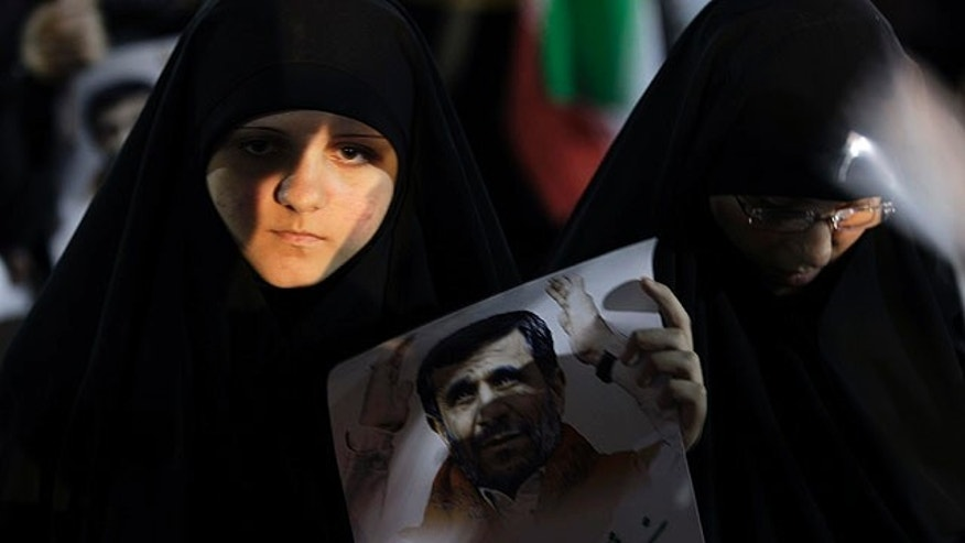 Oct. 13, 2010:  A Hezbollah Supporter holds a poster of Iranian President Mahmoud Ahmadinejad, before Ahmadinejad's speech during a rally organized by Hezbollah at the southern suburb of Beirut, Lebanon.