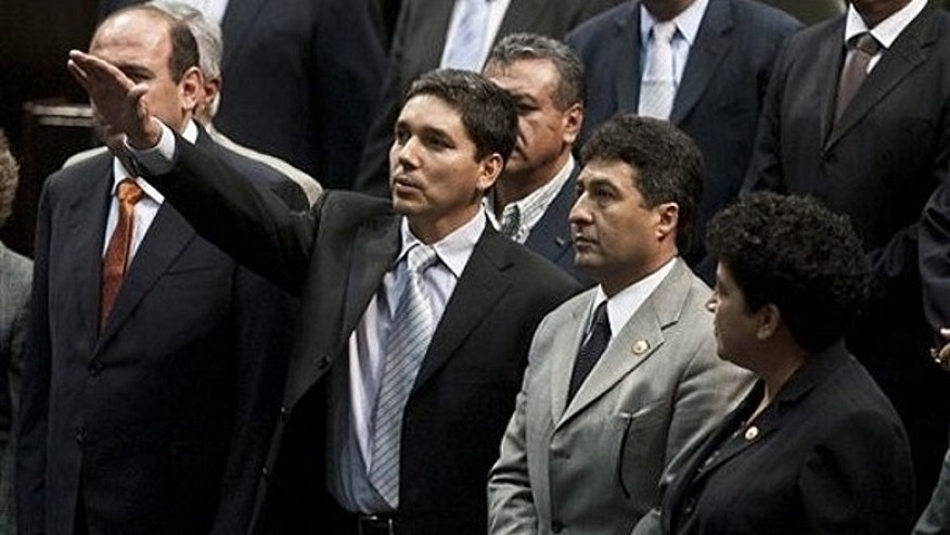 Sept. 23: Julio Cesar Godoy Toscano, center, raises his hand as he is sworn in as federal congressman at the National Congress in Mexico City.