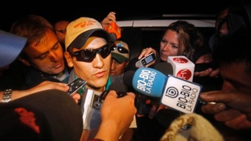 Rescued miner Carlos Mamani, from Bolivia, is surrounded by the press as he arrives to his home in Copiapo, Chile, Thursday Oct. 14, 2010.  Rescued miners are beginning to return to their homes while some remain in the hospital for observation.  (AP Photo/Natacha Pisarenko)