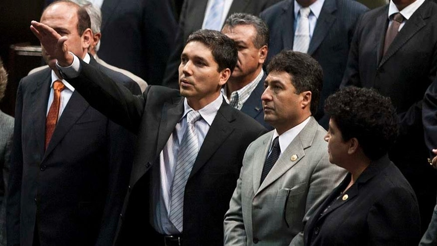 Julio Cesar Godoy Toscano, center, raises his hand as he is sworn in as federal congressman at the National Congress in Mexico City, Thursday Sept. 23, 2010. Godoy, who is wanted by federal authorities for alleged links to drug cartels, evaded a police operation to try to prevent him from being sworn in and gain congressional immunity. (AP Photo/Fernando Castillo)