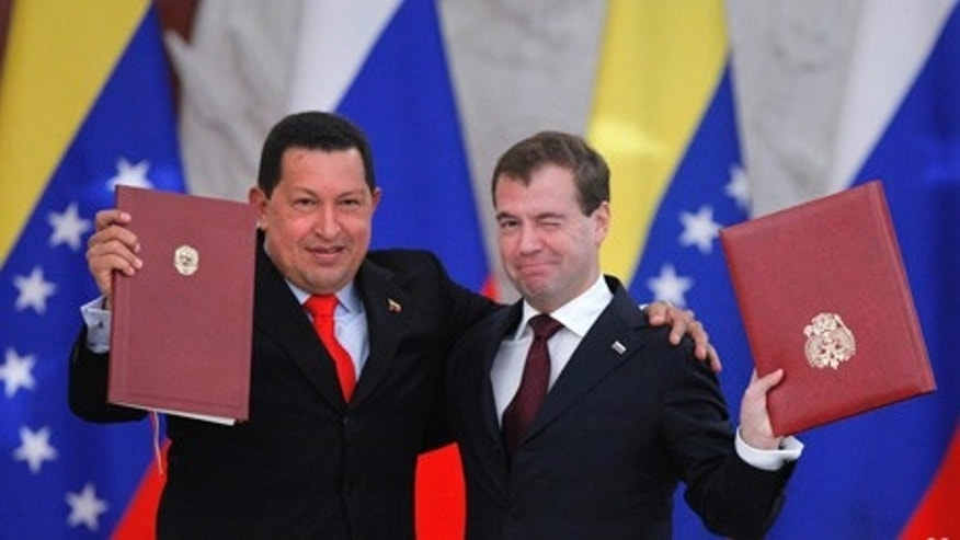 Russian President Dmitry Medvedev, right, and his Venezuelan counterpart Hugo Chavez show signed documents during their meeting in Moscow, Russia, Friday, Oct. 15, 2010. Chavez reached a deal with Russia on Friday to build the South American country's first nuclear plant and negotiated other energy agreements. Medvedev sought to preempt questions about why the Venezuela rich in oil and gas would need nuclear power by saying the deal would help Caracas reduce its dependence on global market fluctuations.  (AP Photo/Alexander Zemlianichenko)