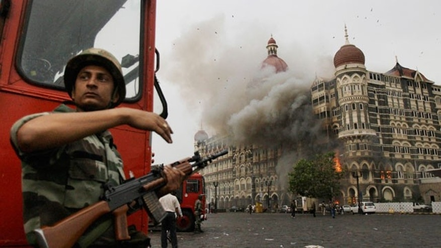 In this Nov. 29, 2008 file photo, an Indian soldier takes cover as the Taj Mahal hotel burns during gun battle between Indian military and militants inside the hotel in Mumbai, India.