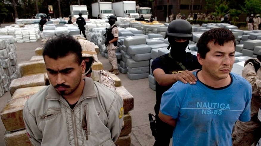 Oct. 18: Soldiers and police guard detainees next to packages of seized marijuana during a presentation for the media in Tijuana, Mexico.