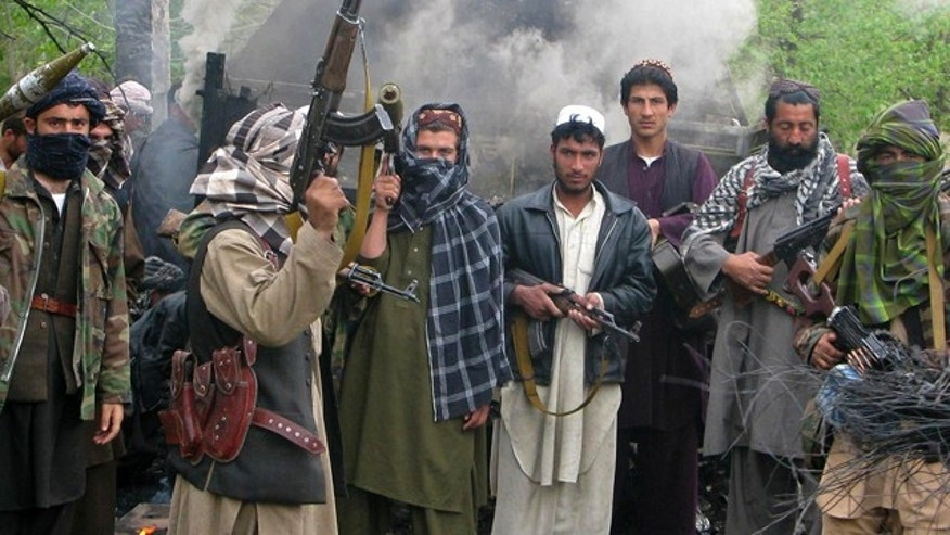 FILE: Taliban insurgents pose in front of a burning German military vehicle in northern Kunduz Province.