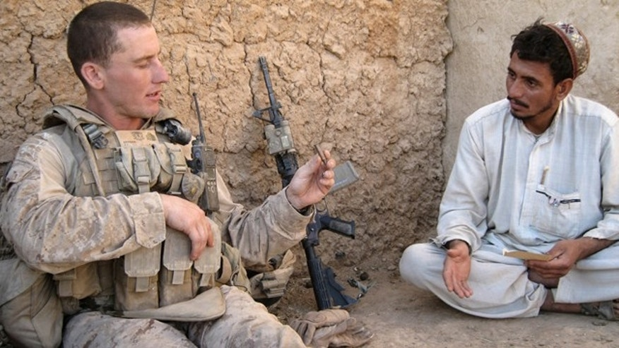 Sept. 26: U.S. Marine Sgt. Jeffrey Benson, left, 34, of Medina, Ohio, holds a spent bullet casing found after a gun battle while he interrogates a resident of Marjah, Afghanistan.