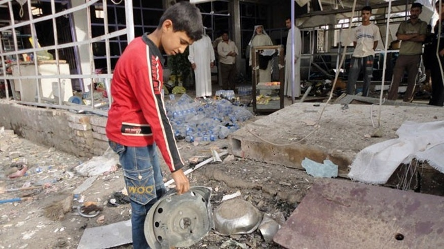 Oct. 7: A boy examines the wreckage of a bomb after an attack hit a vegetable market south of Baghdad.