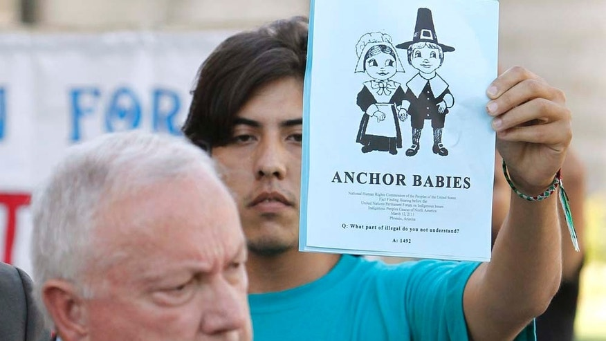 Arizona state Sen. Russell Pearce, R-Mesa, left, talks during a news conference about efforts by state legislators to propose legislation to deny U.S. citizenship to children of illegal immigrants, as protester Abraham Venzor-Hernandez, of the Puente movement, stands in the background Tuesday, Oct. 19, 2010, in Phoenix.  The efforts by the state legislators come amid calls to change the U.S. Constitution's 14th Amendment, which grants automatic citizenship to U.S.-born children of illegal immigrants. (AP Photo/Ross D. Franklin)