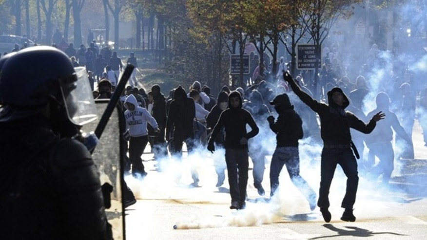 Oct. 21: Youth throw stones at anti-riot policemen amid teargas in Nanterre, a Paris suburb.
