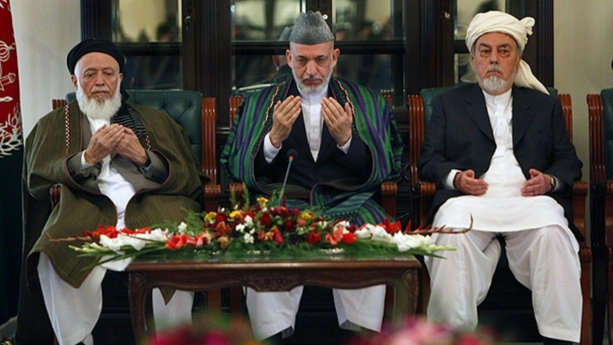 Oct. 7: Afghan President Hamid Karzai, center, prays with members of the Afghanistan peace council in Kabul.