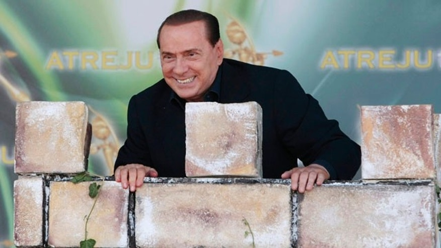 September 12: Italian Premier Silvio Berlusconi leans against a mock tower during a People of Freedom party meeting in Rome. (AP)
