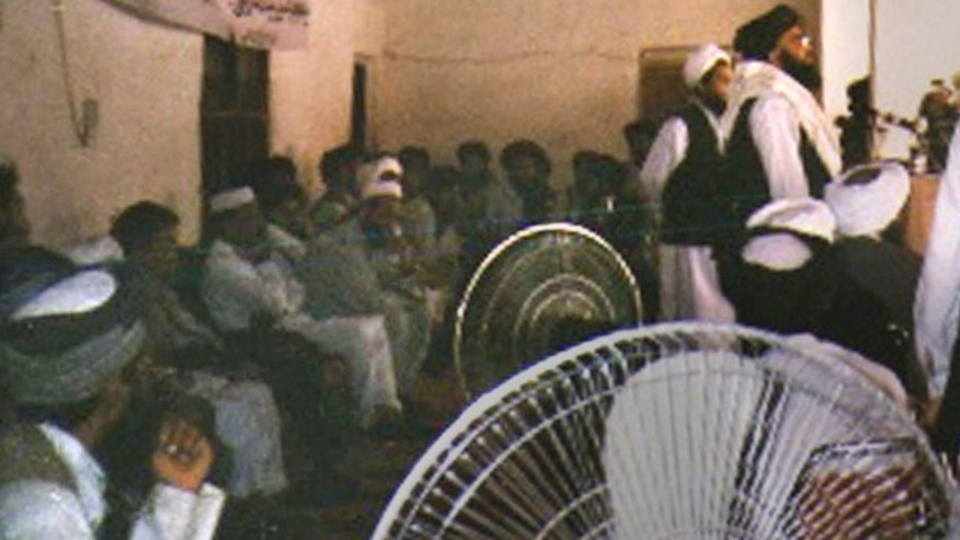 This undated photo originally received by the Associated Press on July 21, 2003, shows former Taliban governor of eastern Nangarhar province and No. 3 in the Taliban hierarchy Maulvi Abdul Kabir, at right with  black turban and glasses, addressing the faithful in the tribal border regions of Pakistan, not far from the border with Afghanistan.