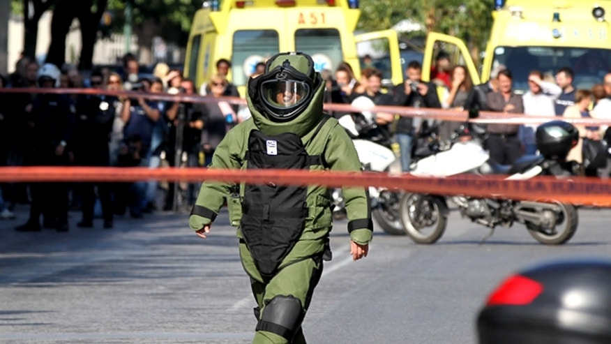 A police explosive expert prepares a controlled blast in Athens, Monday, Nov. 1, 2010. A woman was wounded after a package exploded at a private delivery company, while two other suspected mail bombs were destroyed by police in controlled blasts in the capital, police officials said. The two men suspected of taking part in the attacks were arrested, carrying handguns, wigs, and one of them was also wearing a bulletproof vest, police said.