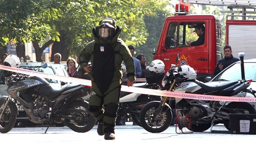 Nov. 1: A police officer prepares for a controlled explosion of a suspect package in Athens, Greece.