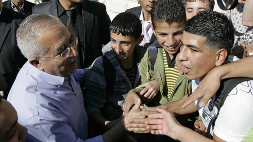 Palestinian Prime Minister Salam Fayyad is surrounded by media and supporters as he visits a school in the West Bank village of Dahiat Al-Barid on the outskirts of Jerusalem, Tuesday, Nov. 2, 2010.