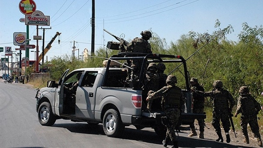 Nov. 5: Navy marines walk behind an armored pick-up truck during a gunfight with alleged cartel members in the northern border city of Matamoros, Mexico. During the operation, Mexican marines killed reputed Gulf cartel leader and one of Mexico's most-wanted drug lords, Antonio Ezequiel Cardenas Guillen.