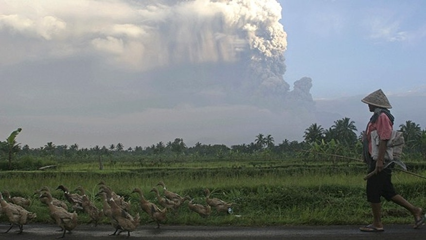 Nov. 4: A villager watchs as volcanic material from the eruption of Mount Merapi burst into the air in Wukirsari, Indonesia.